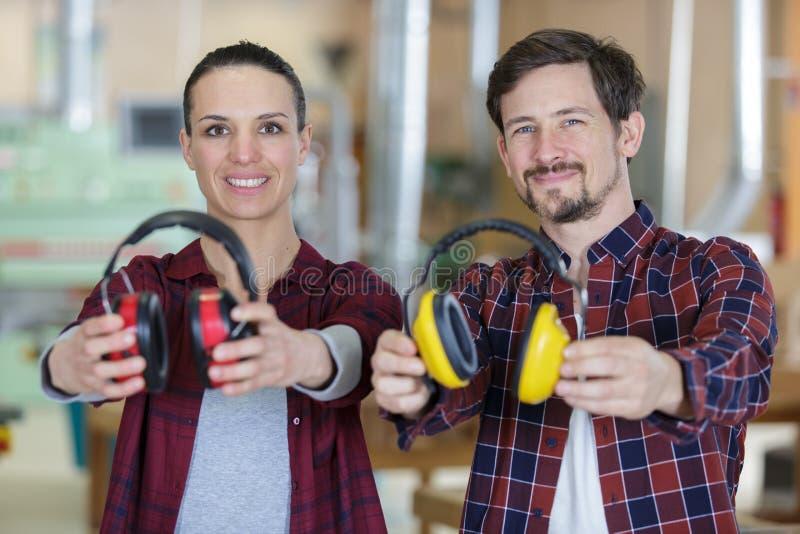 Twee arbeiders die voorwaarts hun oorbeschermers houden stock afbeeldingen