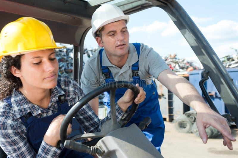 Twee arbeiders die vorkheftruck in openlucht gebruiken stock afbeeldingen