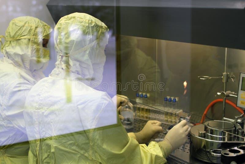 Twee arbeiders in een beschermende kledingslaboratorium voeren onderzoek uit royalty-vrije stock afbeeldingen