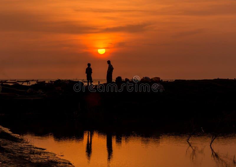 Twee arbeiders spreken erachter onder zich en de zonsondergang royalty-vrije stock afbeelding