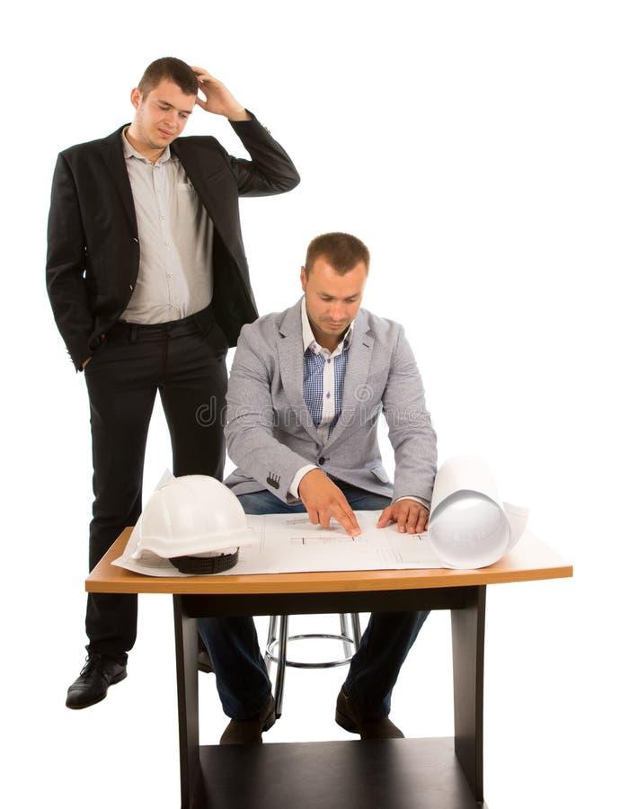 Twee architecten of bouwers die aan een plan werken stock afbeeldingen