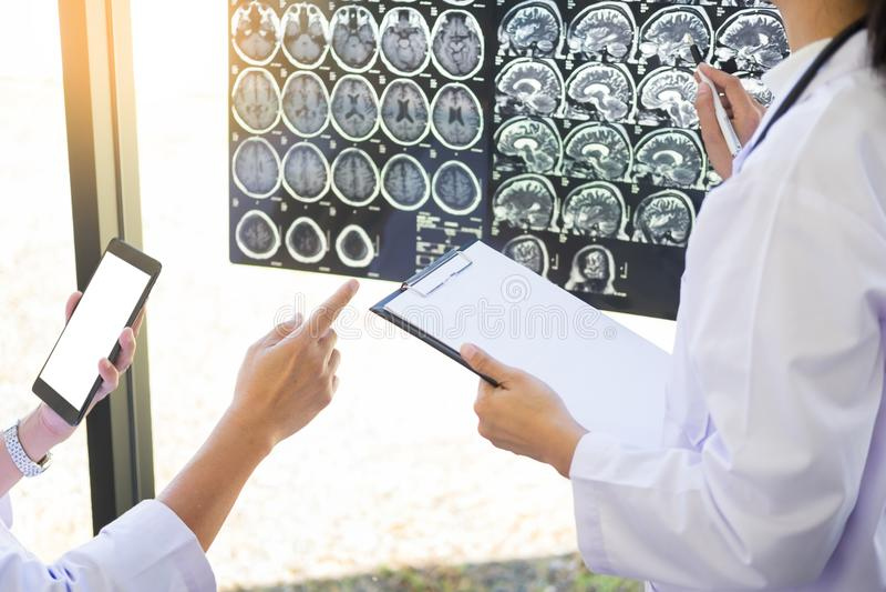 Twee artsen die een aftasten of een röntgenstraal analyseren filmen of verklaart een CT sca stock foto's