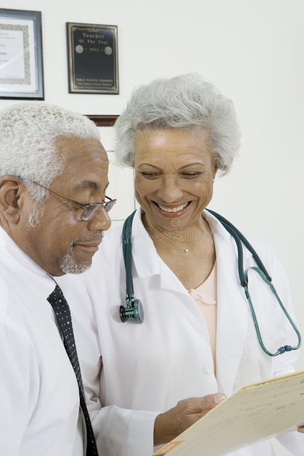 Twee Artsen die een Document in Kliniek bekijken stock afbeeldingen
