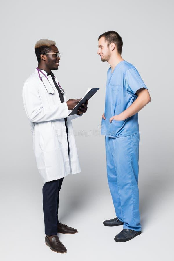 Twee artsen die en elkaar ontmoeten raadplegen over grijze achtergrond Kaukasische pacient arts en het Afro-Amerikaanse arts spre royalty-vrije stock foto