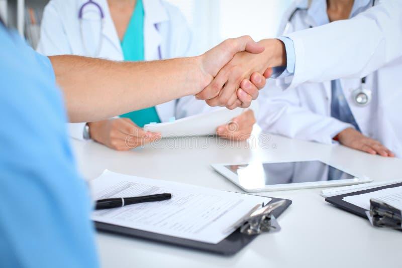 Twee artsen die handen schudden aan elkaar op vergadering Groepswerk en overeenkomst in geneeskunde royalty-vrije stock foto's