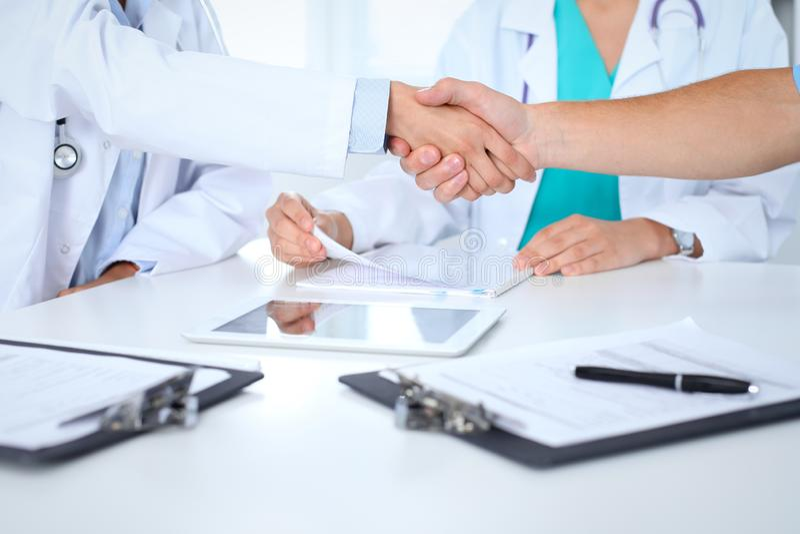 Twee artsen die handen schudden aan elkaar op vergadering Groepswerk en overeenkomst in geneeskunde stock afbeelding