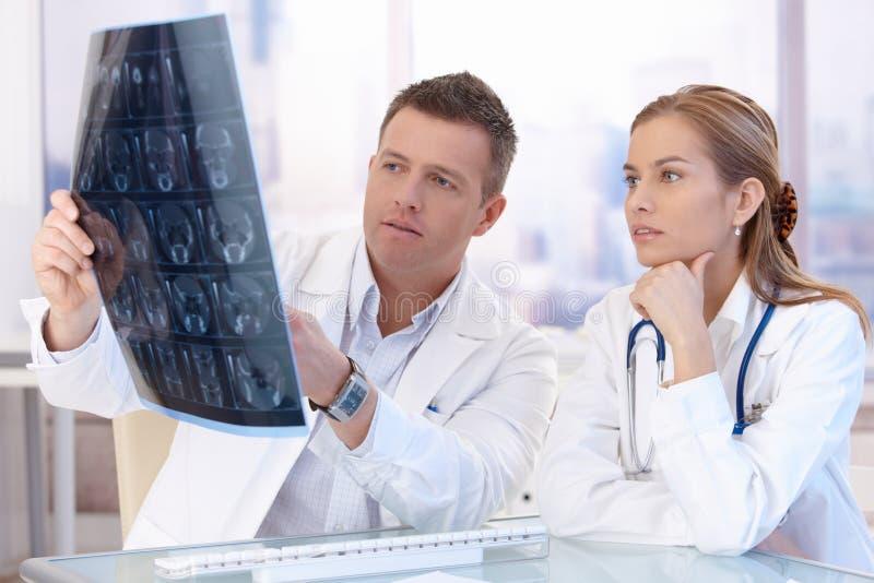 Twee artsen die het x-ray beeld raadplegen bestuderen royalty-vrije stock fotografie