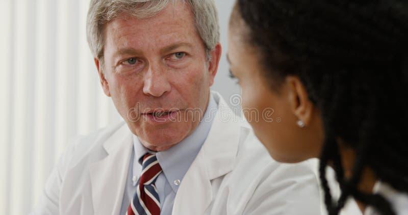 Twee artsen die hun professionele adviezen over het dossier van de patiënt delen royalty-vrije stock fotografie