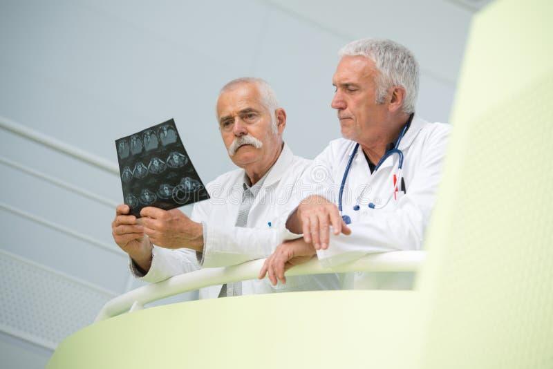 Twee artsen die röntgenstraal bekijken stock foto's