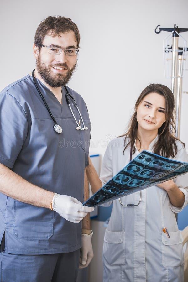 Twee artsen zenden Röntgenstraalfoto van de patiënt uit om het probleem te identificeren Professioneel gesprek, overleg met artse stock fotografie