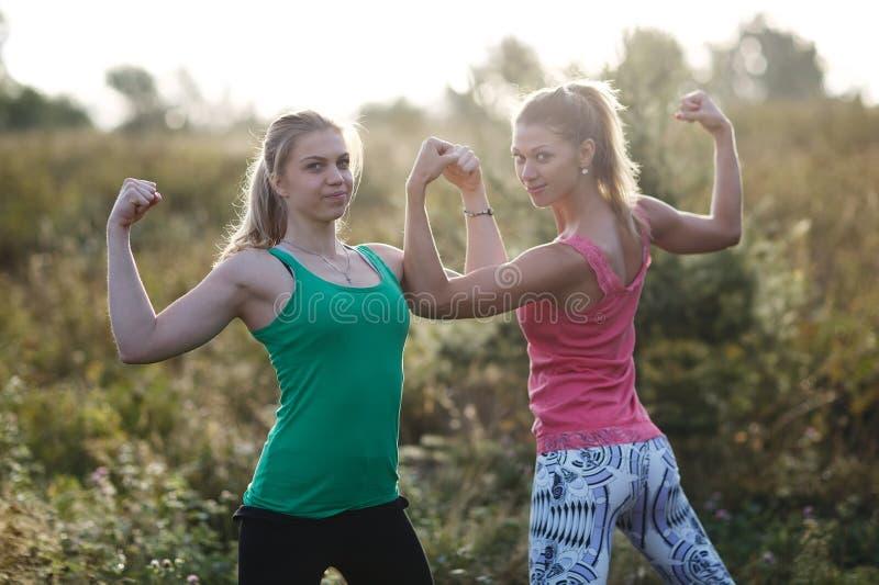 Twee atletische meisjes die hun wapenspieren buigen stock foto