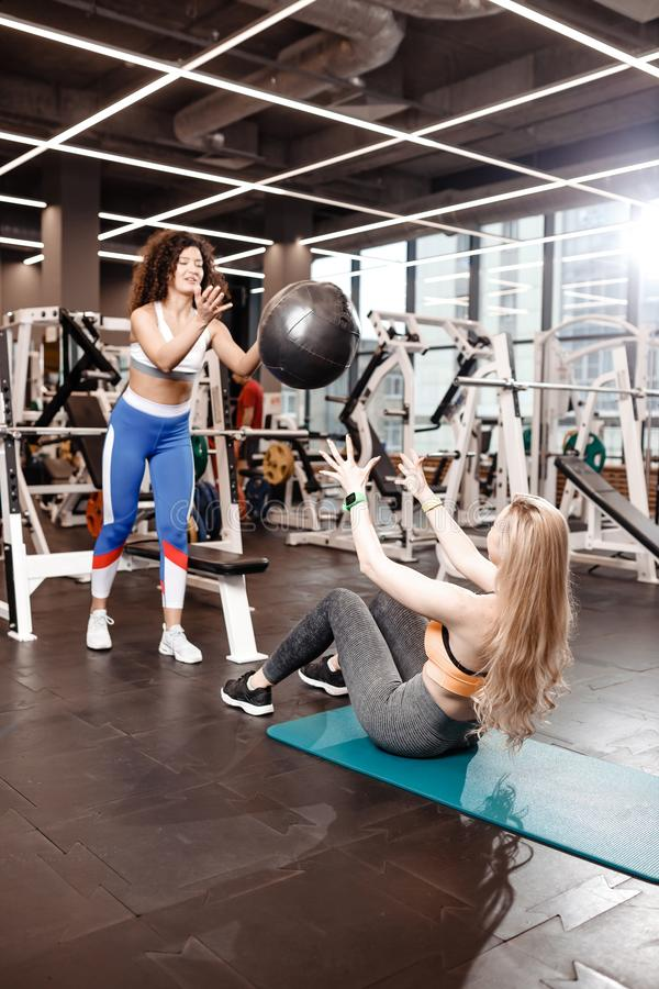 Twee atletische meisjes gekleed in een sportkleding doen oefeningen voor de pers op de mat voor geschiktheid met geschiktheids bi royalty-vrije stock foto