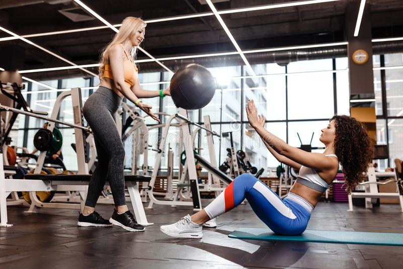 Twee atletische meisjes gekleed in een sportkleding doen oefeningen voor de pers op de mat voor geschiktheid met geschiktheids bi royalty-vrije stock foto's
