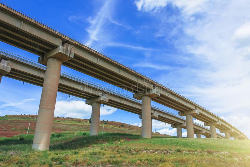 Twee autosnelwegbrug, viaduct steunt in de vallei tussen de groene heuvels, vervoersinfrastructuur stock fotografie