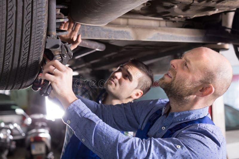 Twee autowerktuigkundigen op workshop stock foto's