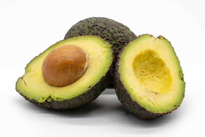 Twee avocado's, een geheel fruit en gehalveerd met steen stock foto