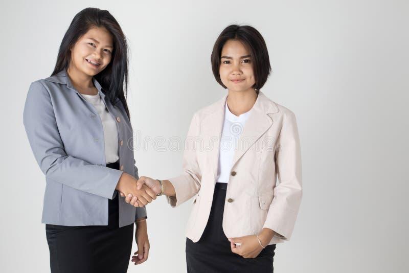 Twee Aziatische Bedrijfsvrouwen die Handen schudden royalty-vrije stock afbeeldingen