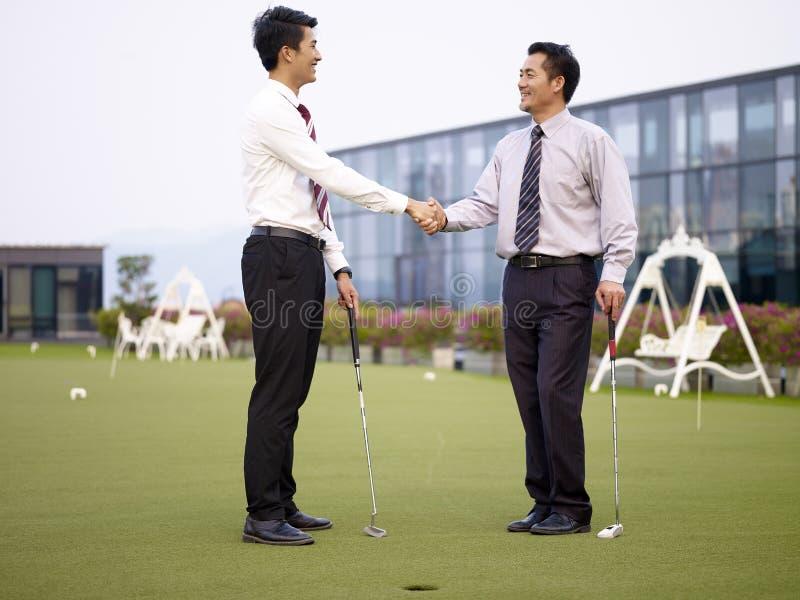 Twee Aziatische collectieve stafmedewerkers die handen op golfcursus schudden stock foto's