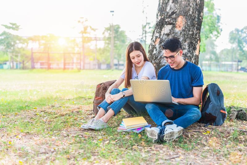 Twee Aziatische jonge universiteitsmensen die over thuiswerk en definitief onderzoek voor het testen met laptop bespreken Onderwi stock afbeelding