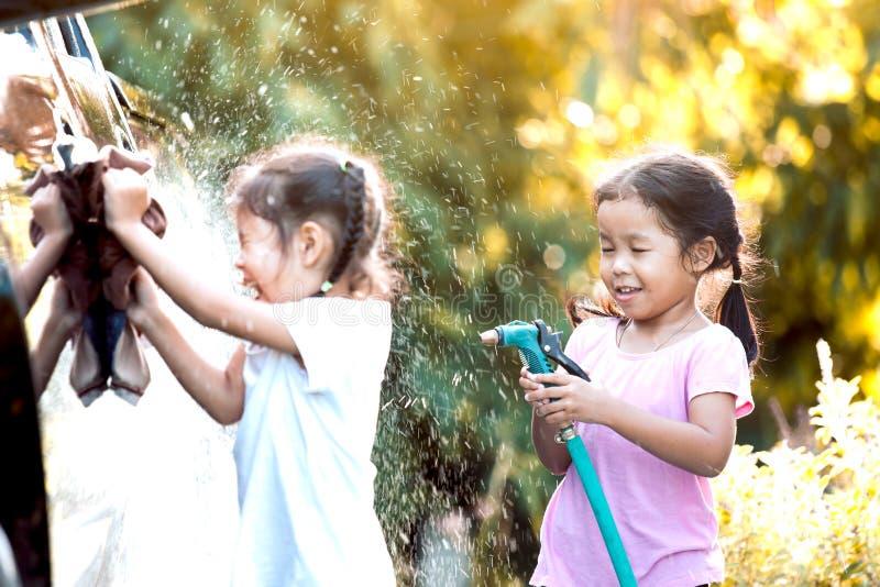 Twee Aziatische kindmeisjes die pret hebben om de auto van de ouderwas te helpen stock foto's