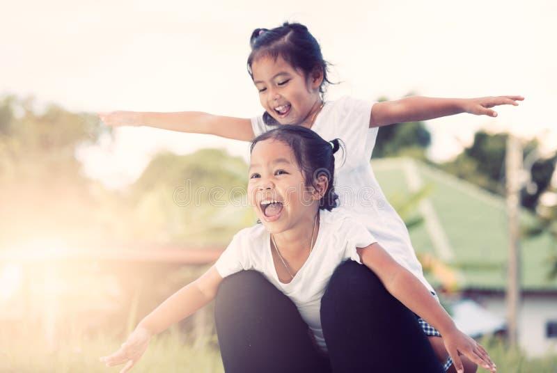 Twee Aziatische kindmeisjes die pret hebben om op moeder` s been te vliegen royalty-vrije stock foto's