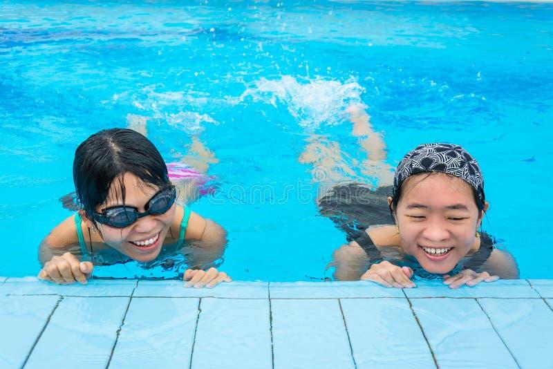 Twee Aziatische meisjes bespatten water in het zwembad royalty-vrije stock foto