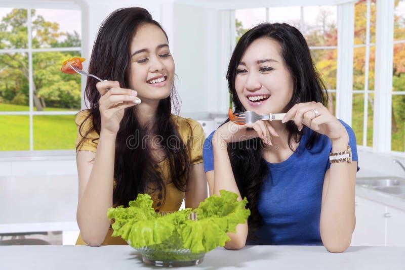 Twee Aziatische meisjes eet verse salade stock foto
