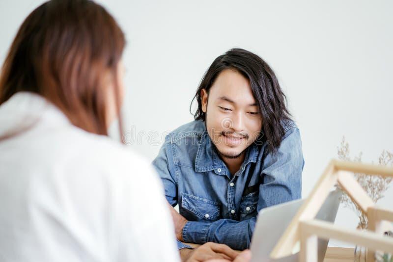 Twee Aziatische mensen die bespreking spreken en tonen detail op laptop royalty-vrije stock foto's