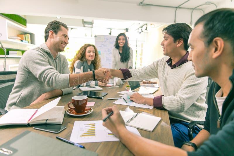 Twee Aziatische zakenlieden andCatch de Kaukasische hand gelukkig Afte royalty-vrije stock foto's