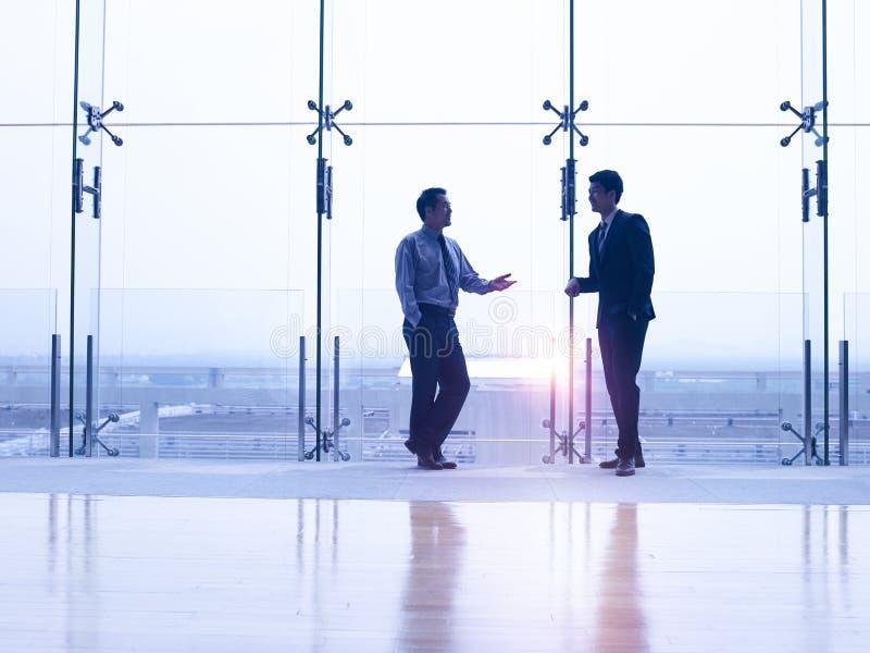 Twee Aziatische zakenlieden die door de vensters spreken royalty-vrije stock foto's