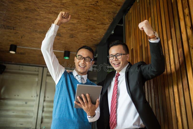 Twee Aziatische zakenmantribune en het bekijken tablet, zij vrolijk en gevierd zijn succesvol in opdracht royalty-vrije stock foto's