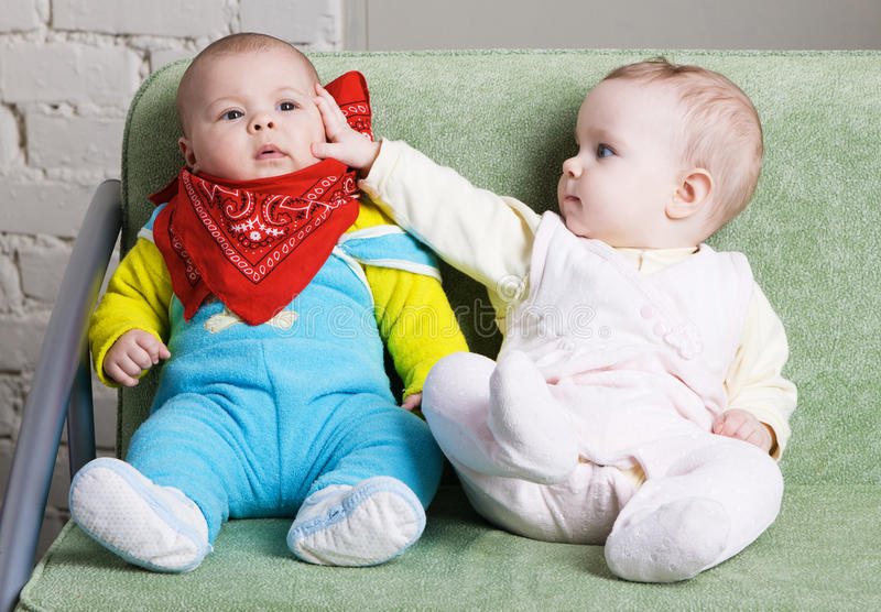 Twee babys die op een bank samen zitten royalty-vrije stock afbeelding