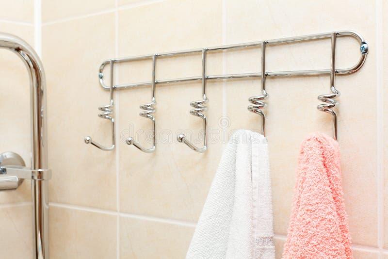 Twee badstofhanddoeken die op haken hangen stock foto's