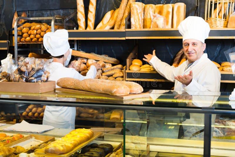 Twee bakkers bij de teller bij bakkerij royalty-vrije stock afbeeldingen