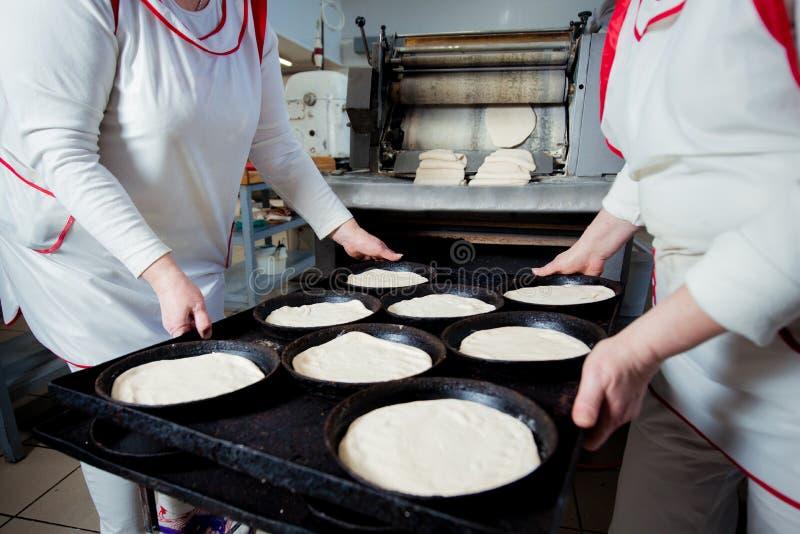 Twee bakkers houden bakselvormen met pizzaspaties stock foto