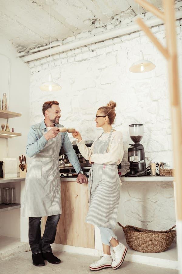 Twee baristas die schorten dragen die koffie samen drinken stock fotografie