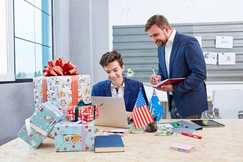 Twee beambten achter het het werkproces naast de dozen van de Kerstmisgift stock afbeelding