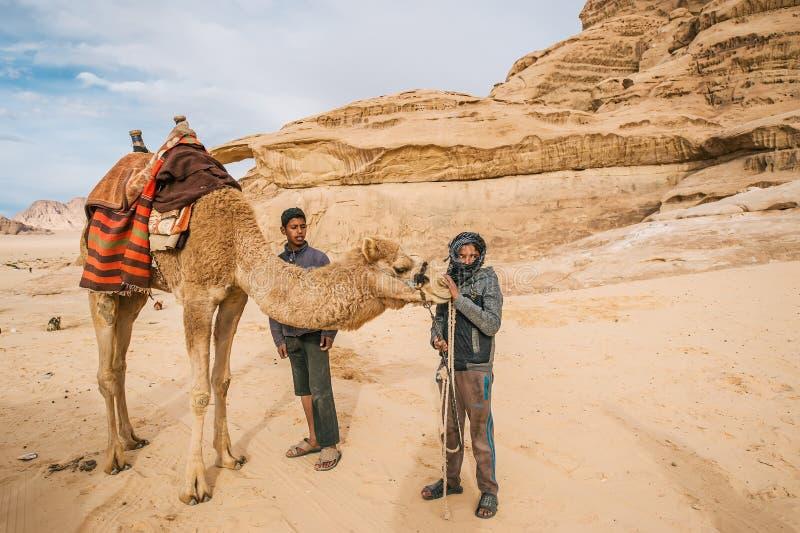 Twee Bedouin mensen die met kameel zich op de achtergrond van rots in Wadi Rum bevinden verlaten jordani? stock foto's