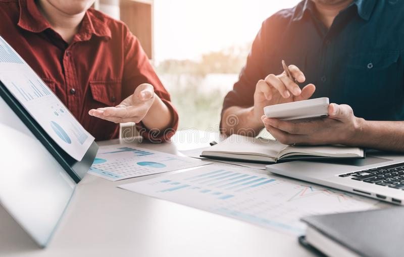 Twee bedrijfsmensen berekenen inkomens financiële kosten van het bedrijf op bureau bij de bureauruimte royalty-vrije stock afbeelding
