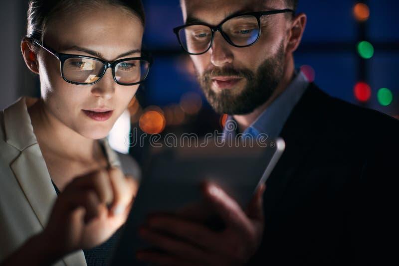 Twee bedrijfsmensen die aan tablet bij nacht werken stock foto's