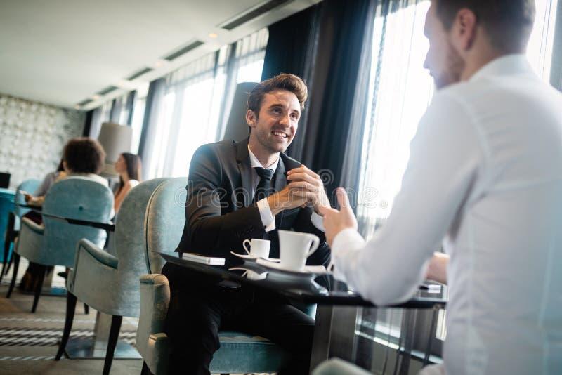 Twee bedrijfsmensen die bij koffiewinkel zitten die project bespreken royalty-vrije stock afbeeldingen