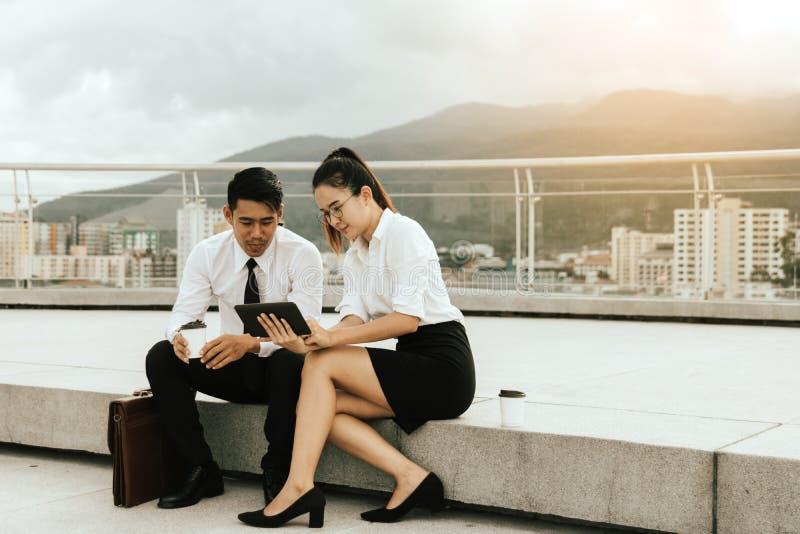Twee bedrijfsmensen die digitale tablet samen gebruiken op buiten bedrijfskantoor royalty-vrije stock foto's