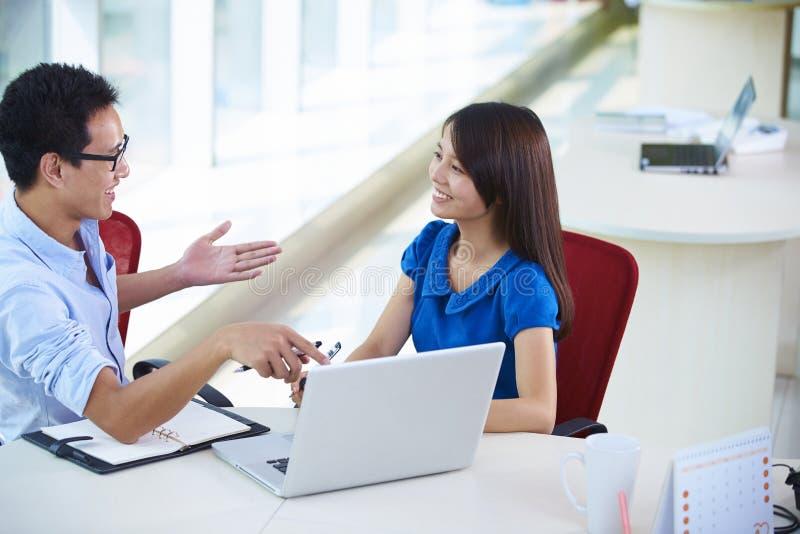 Twee bedrijfsmensen die in het bureau spreken stock afbeelding