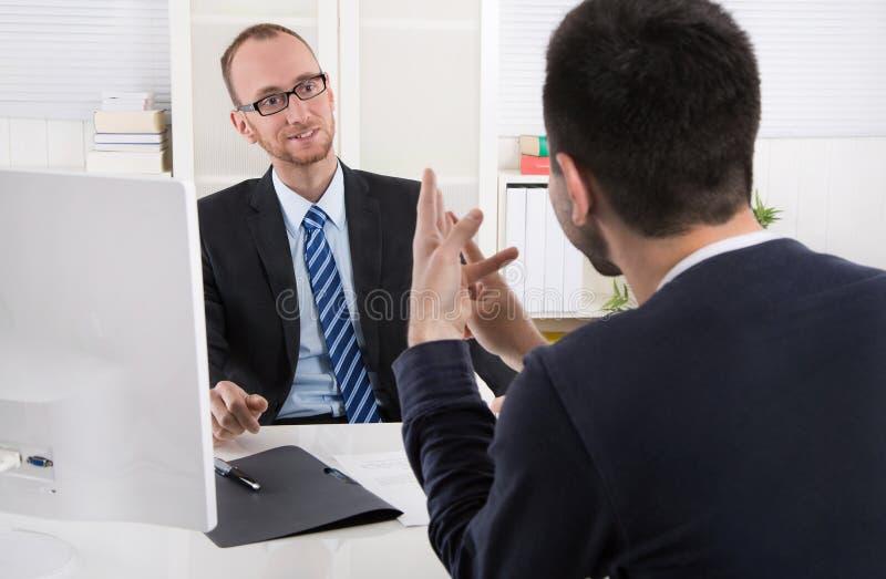 Twee bedrijfsmensen die in het bureau zitten: vergadering of baangesprek royalty-vrije stock afbeeldingen