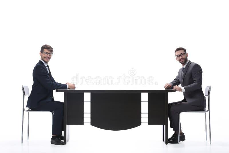 Twee bedrijfsmensen die iets bespreken die bij de lijst zitten royalty-vrije stock afbeelding
