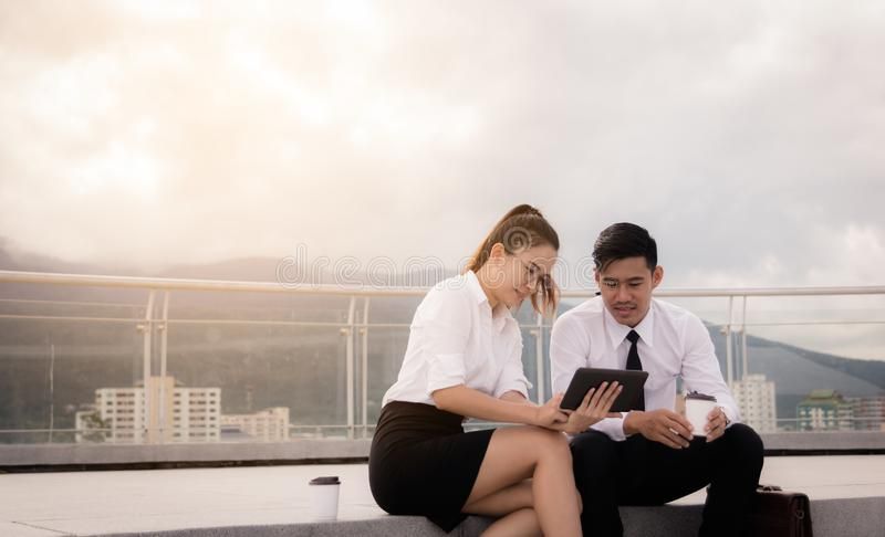 Twee bedrijfsmensen die op dakvloer zitten en digitale tablet samen gebruiken op buiten bedrijfskantoor royalty-vrije stock foto's
