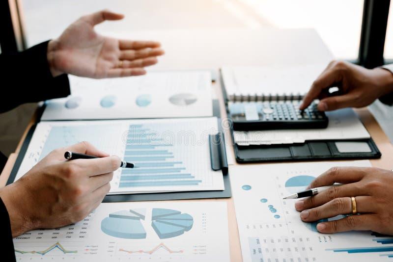 Twee bedrijfsmensen die over grafiek en analyse over het bedrijf van de financi?nbegroting spreken en calculator in bureauruimte  stock afbeelding