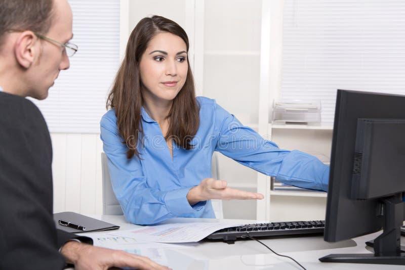 Twee bedrijfsmensen die samen bij bureau spreken - adviseur en custo royalty-vrije stock afbeeldingen