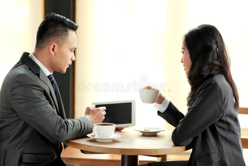 Twee bedrijfsmensen die tijdens koffiepauze samenkomen stock foto