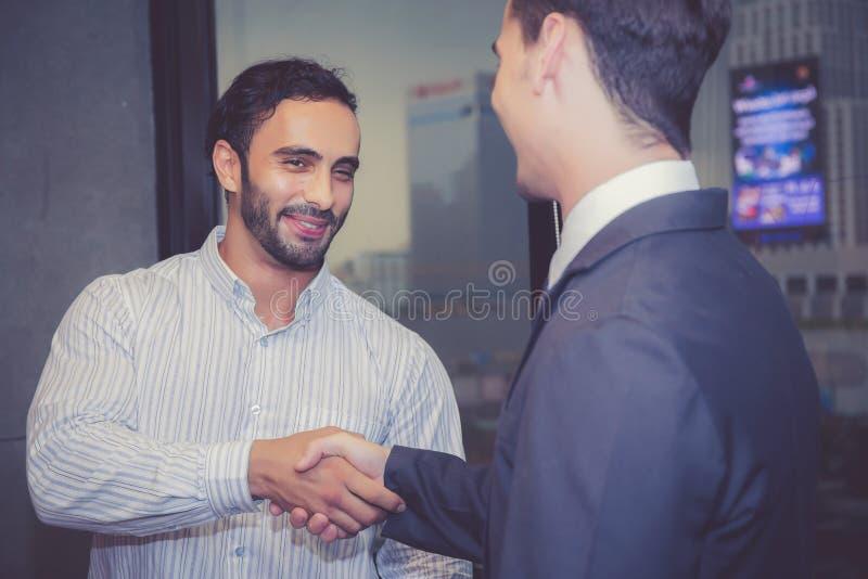 Twee bedrijfsmensenmensen die hand met succes, overeenkomst schudden van royalty-vrije stock afbeelding